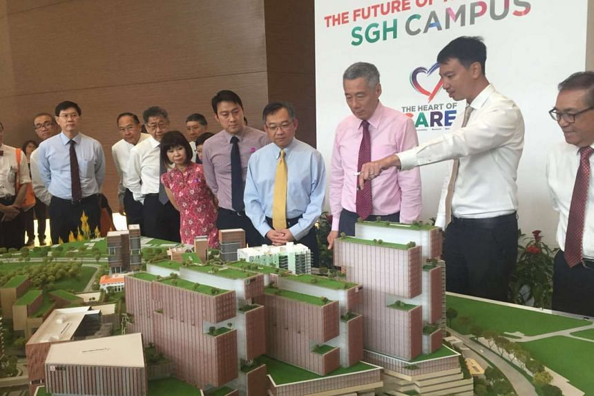 Prime Minister Lee Hsien Loong (third from right), Health Minister Gan Kim Yong (centre) and Senior Minister of State for Health Amy Khor (sixth from right) viewing a scale model of SGH's new masterplan.