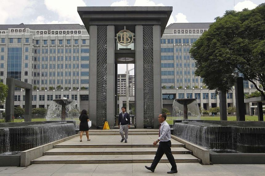 People walk near an entrance to Bank Indonesia's headquarters in Jakarta, Indonesia, on Jan 14, 2016.