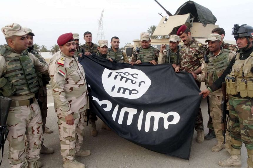 Iraqi security forces with an Islamic State flag they pulled down in the city of Ramadi on Feb 1.