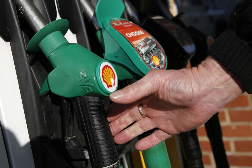 A man reaches for an unleaded petrol nozzle at a petrol station in Hook, near Basingstoke on Jan 20, 2016.