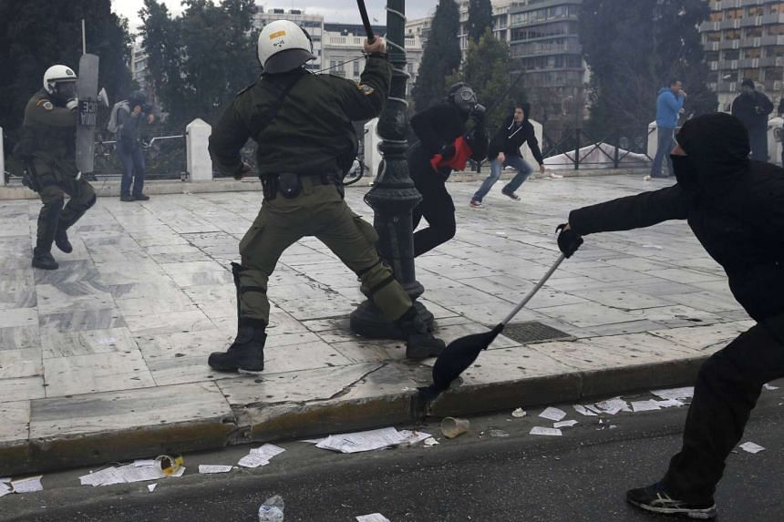 Masked demonstrators clash with a riot police in Syntagma Square, Athens.