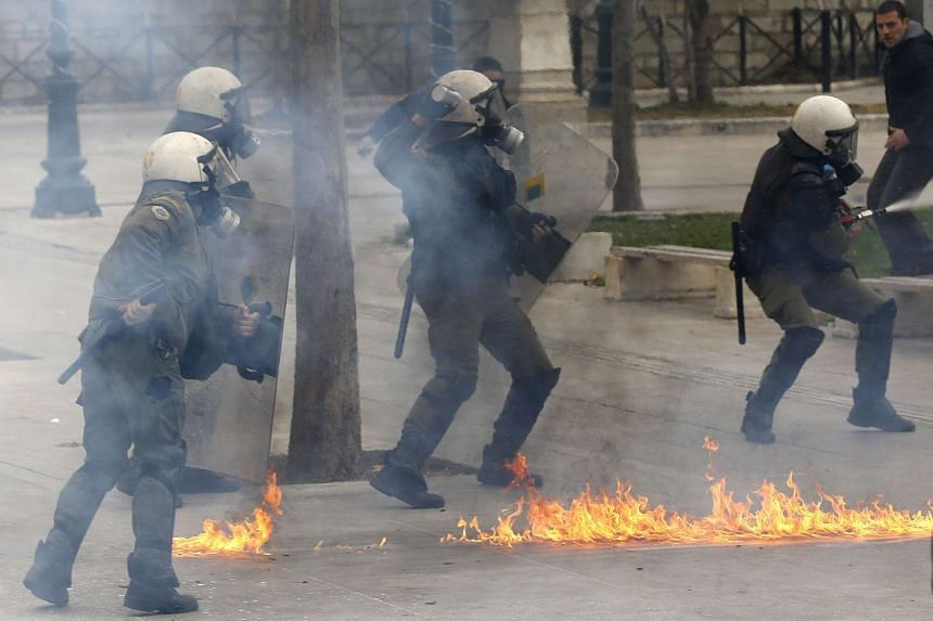 Riot police dodge petrol bombs thrown by masked protesters.