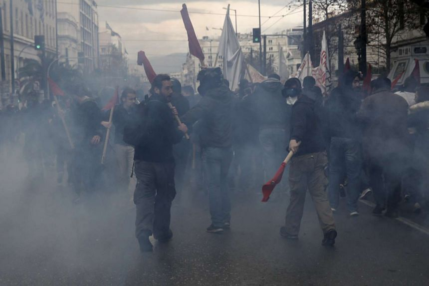 Protesters walk amid tear gas smoke during clashes.