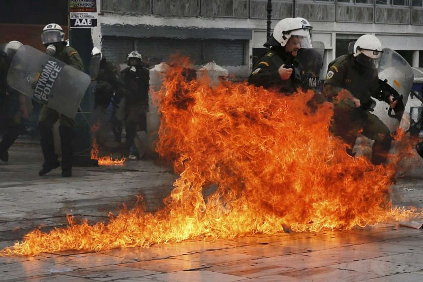 Riot police react to petrol bombs thrown by masked youths in Syntagma Square, Athens.