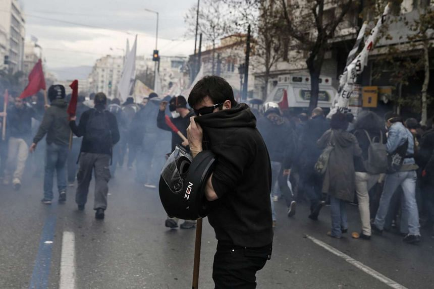 A protester covers his face to avoid breathing tear gas.
