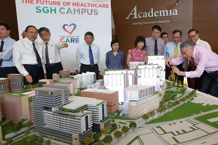Prime Minister Lee Hsien Loong (right) snapping a picture of SGH's masterplan at its unveiling on Feb 5. With him are Health Minister Gan Kim Yong (third from right) and Senior Minister of State for Health Amy Khor (sixth from right).