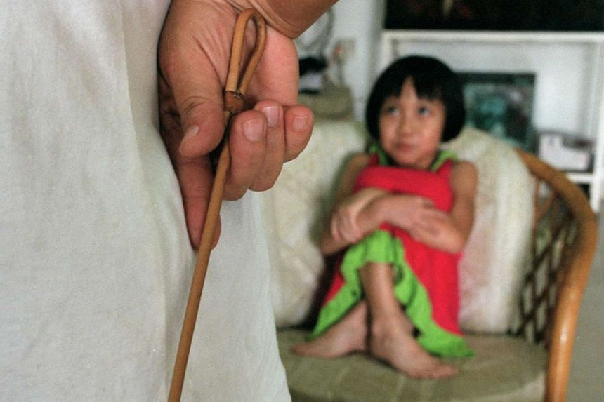 An adult holds a cane in front of a child (posed photo).