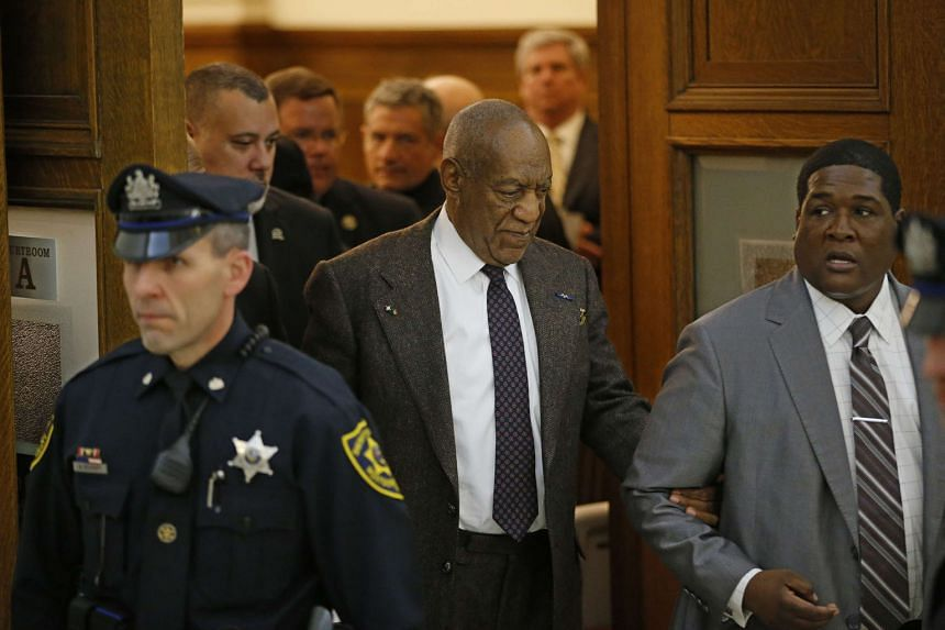 Bill Cosby being led out of the courtroom in Montgomery County Courthouse in Norristown, Pennsylvania, on Wednesday. His lawyers argue that a 2005 deal with a former district attorney means Cosby cannot be prosecuted.
