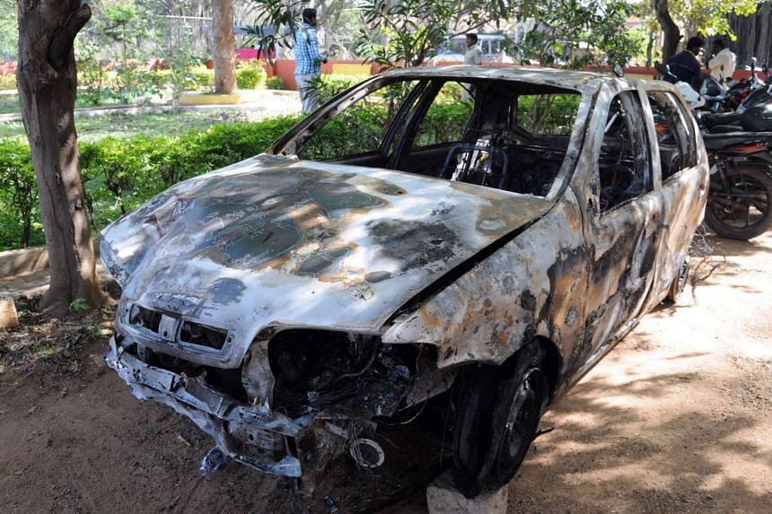 Pedestrians gather near the burnt-out shell of a vehicle at a local police station in Bangalore.