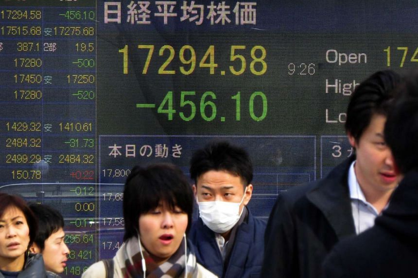 Pedestrians walking past a stock prices board in Tokyo on Feb 3.