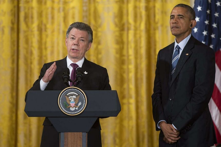 US President Barack Obama (right) listening as Colombian President Juan Manuel Santos speaks at a reception at the White House on Feb 4.