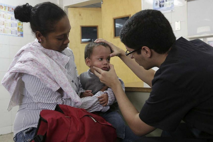 A child suspected to be infected with Zika virus is examined on Feb 4, 2016, in Caracas, Venezuela.