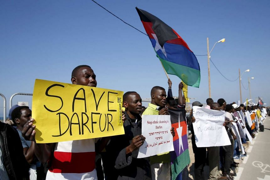 Demonstrators, most of whom from Darfur and Sudan, hold placards as they protest against human rights violation.