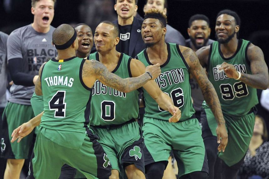 The Boston Celtics celebrate after guard Avery Bradley hit a three-point shot to win the game.