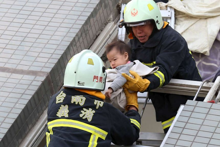 Rescue workers removing a baby from the site where a 17-storey apartment building collapsed after an earthquake hit Tainan, on Feb 6, 2016.