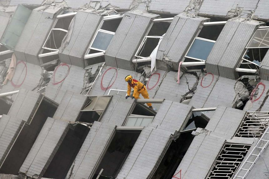 A rescue worker searches for survivors in a collapsed building following a 6.4 magnitude earthquake in Tainan city, south Taiwan on Feb 6, 2016.