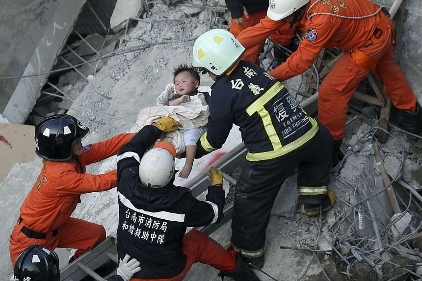 Rescue personnel help a child rescued at the site where a 17-storey apartment building collapsed during the earthquake.