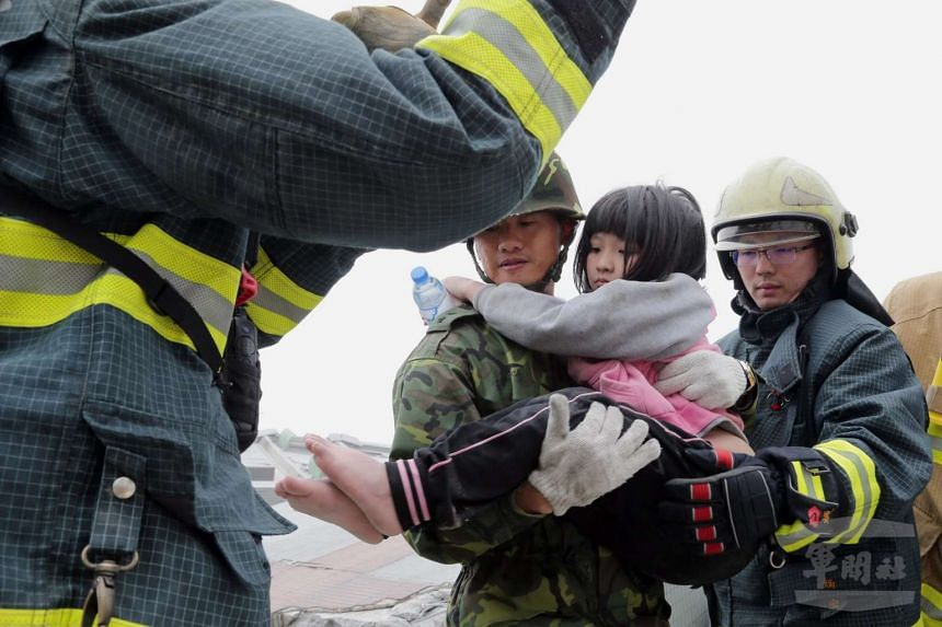 Taiwanese soldiers holding a young girl resuced from a collapsed building in Tainan City, south Taiwan following the quake.