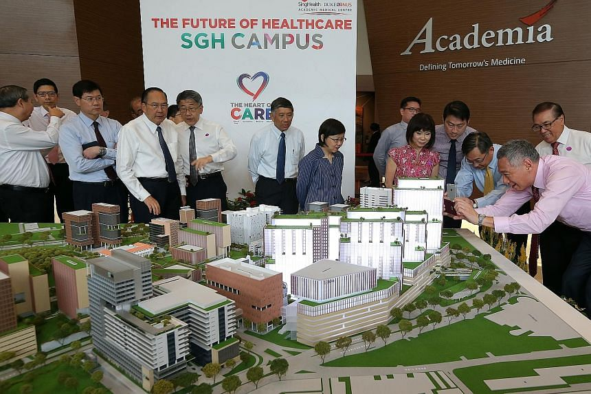 Prime Minister Lee Hsien Loong (right) and Health Minister Gan Kim Yong snapping photos of a model of SGH's campus masterplan yesterday. With them is Senior Minister of State for Health Amy Khor (in pink). More space will be given to areas where the