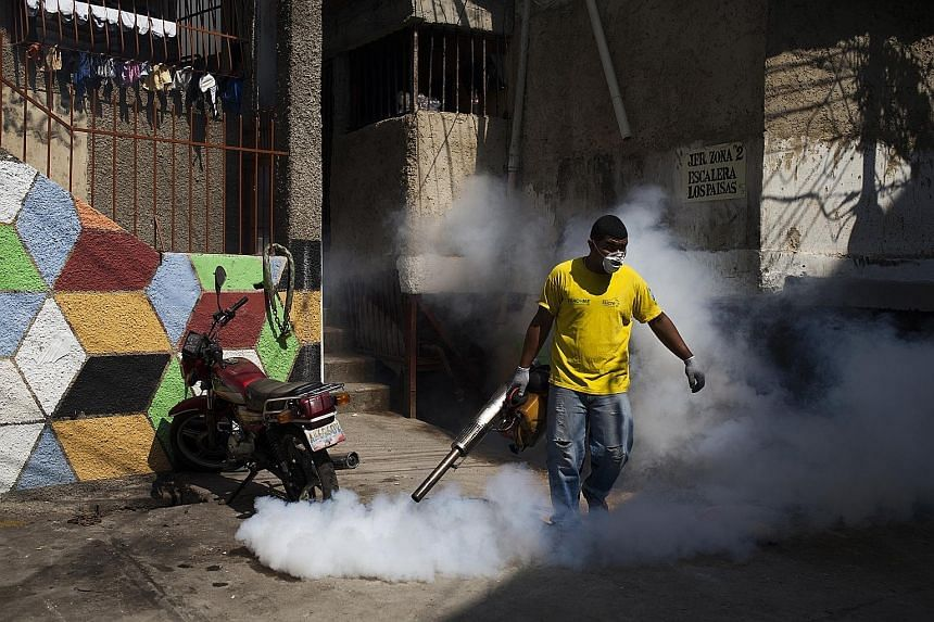 A worker in a neighbourhood in Venezuela's capital, Caracas, spraying insecticide on Wednesday to eradicate mosquitoes. Mosquito-eating sambo fish are being put in home water tanks as one of El Salvador's biological methods to control the insect's po