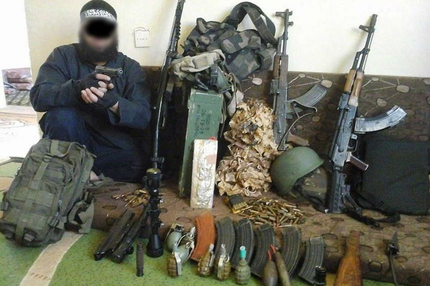 A 34-year old Algerian man poses next to firearms and ammunition in a photo released by police.