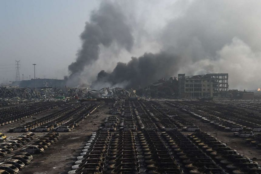 Smoke billows behind rows of burnt out cars at the site of a series of explosions in Tianjin, northern China on Aug 13, 2015.