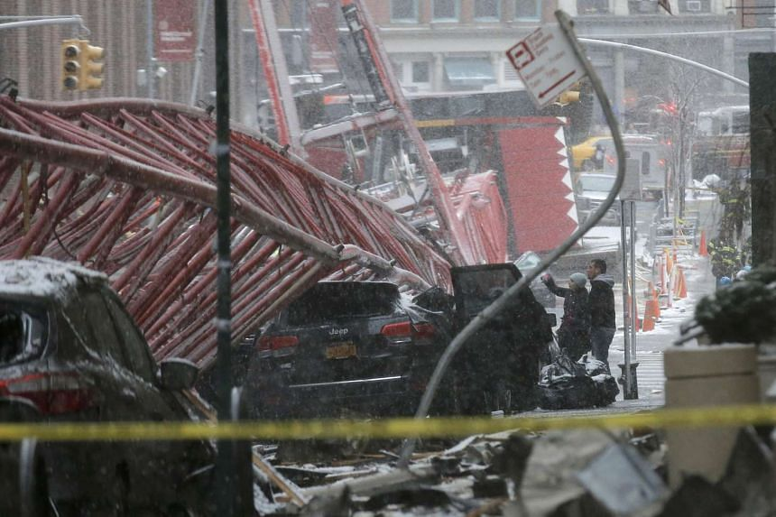 Emergency crews survey the massive construction crane collapse on a street in downtown Manhattan in New York.