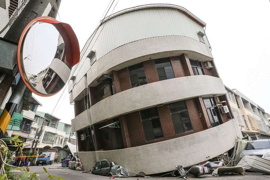 Crushed vehicles are seen under a building that was damaged after a powerful earthquake hit Tainan on Feb 6.