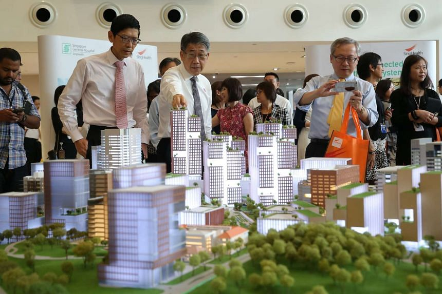Going high-rise: Guests including National University of Singapore president Tan Chorh Chuan (left) taking in a model of SGH's new masterplan, which sees the once sprawling hospital going high-rise to maximise space and efficiency. The tallest buildi