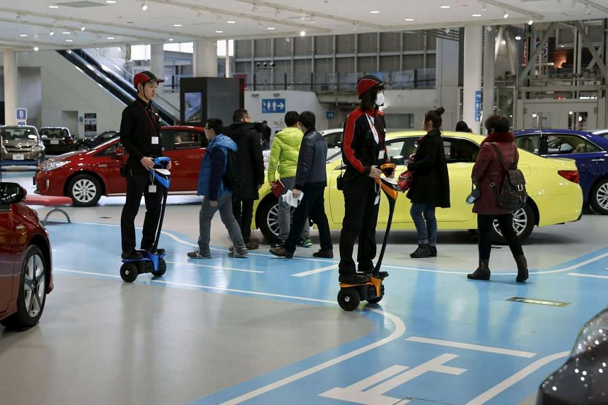 Employees riding on Toyota Motor's Winglet personal mobility devices at its showroom in Tokyo, Japan, yesterday. Toyota last month kept the title of world's top automaker for the fourth straight year after announcing that it sold 10.15 million vehicl