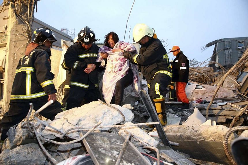 Rescue personnel helping a victim at a damaged building after an earthquake in Tainan, southern Taiwan, on Feb 6, 2016.