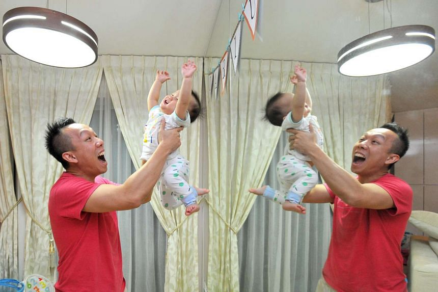 Mr Terence Tan, 37, an algorithmic forex trader, playing with his one-year-old son Darius at home on Feb 5.