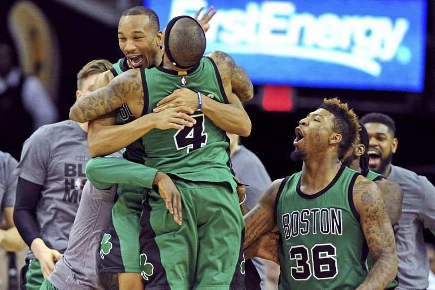Boston Celtics guard Avery Bradley (left) celebrating with guard Isaiah Thomas (No. 4) after making a three-point shot to end the game by beating the Cleveland Cavaliers at the Quicken Loans Arena. The Celtics won 104-103.