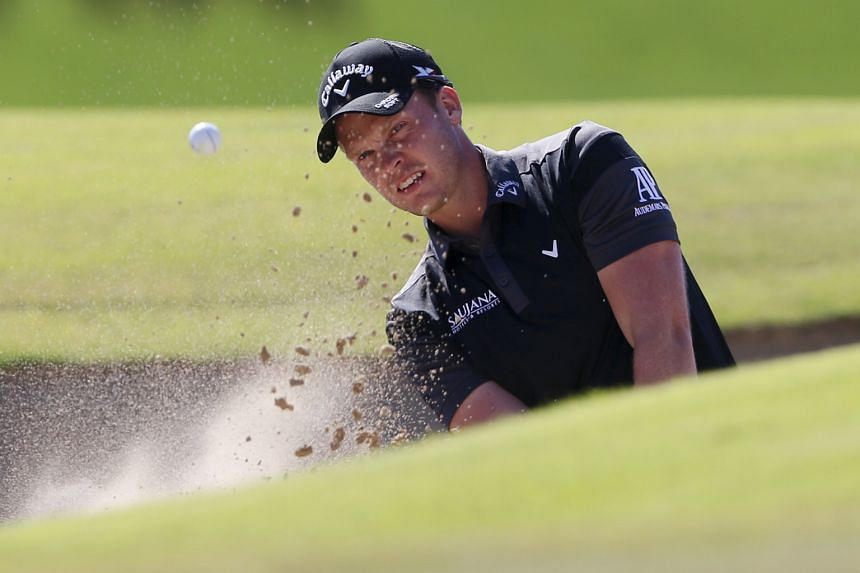 Danny Willett hitting the ball out of the bunker on the sixth hole during the third round of the Dubai Desert Classic. The Englishman, who leads a crowded leader board by a stroke, was second in last year's Race to Dubai.