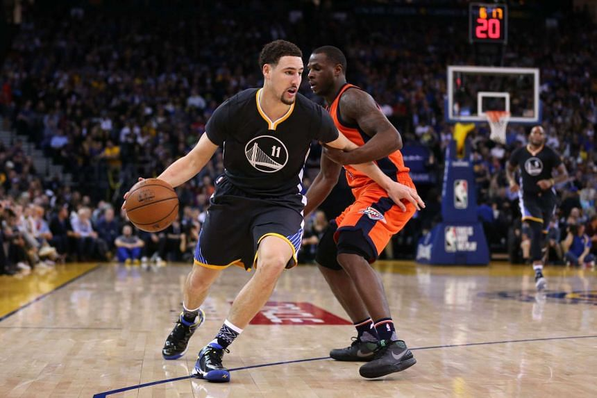 Golden State Warrior's Klay Thompson dribbles the ball past Oklahoma City Thunder's Dion Waiters.
