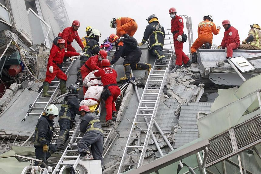 Rescue personnel remove the body of a victim at the site where a 17-storey apartment building collapsed.