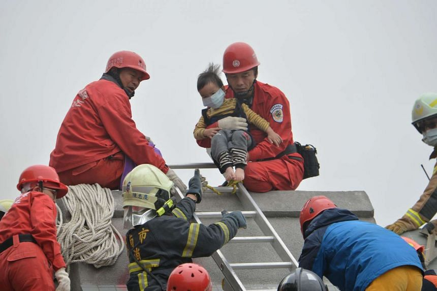 Rescue personnel help a young victim at the site of a collapsed building.