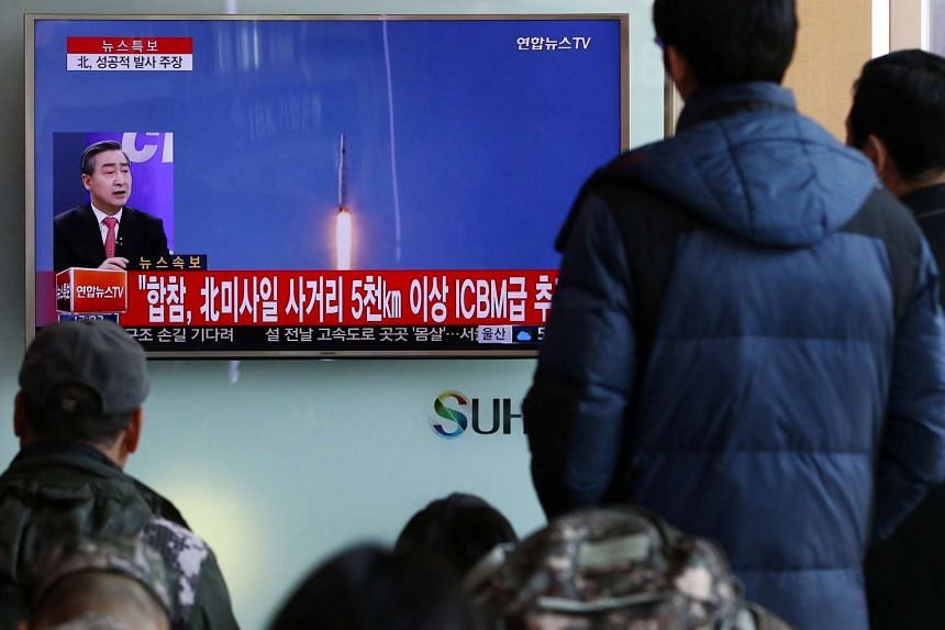 South Koreans watching a news broadcast announcing North Korea's long-range rocket launch at Seoul Station.