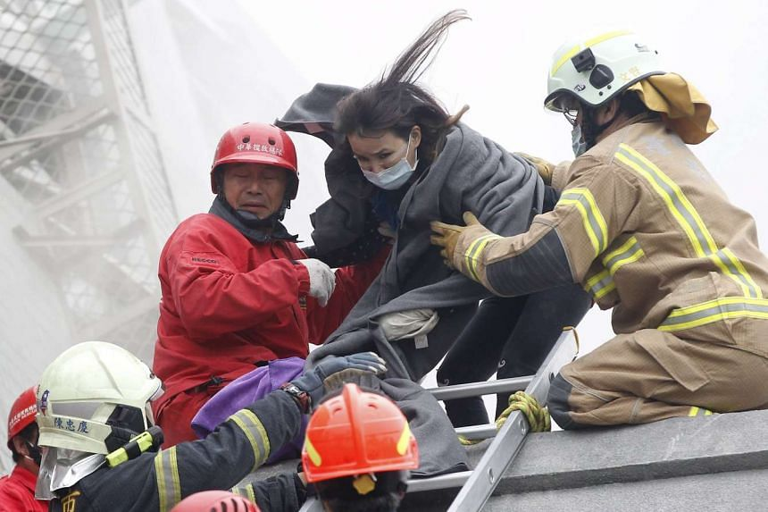 Rescue personnel help a victim at the site where a 17-storey apartment building collapsed.