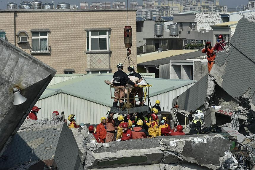 Rescue workers use a crane to transport a survivor found in the rubble at the Wei-kuan apartment complex on Feb 7, 2016.