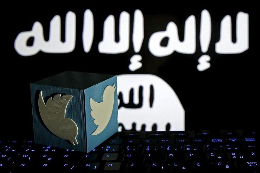 A 3D-printed Twitter logo is seen on a keyboard in front of a computer screen on which an Islamic State flag is displayed.