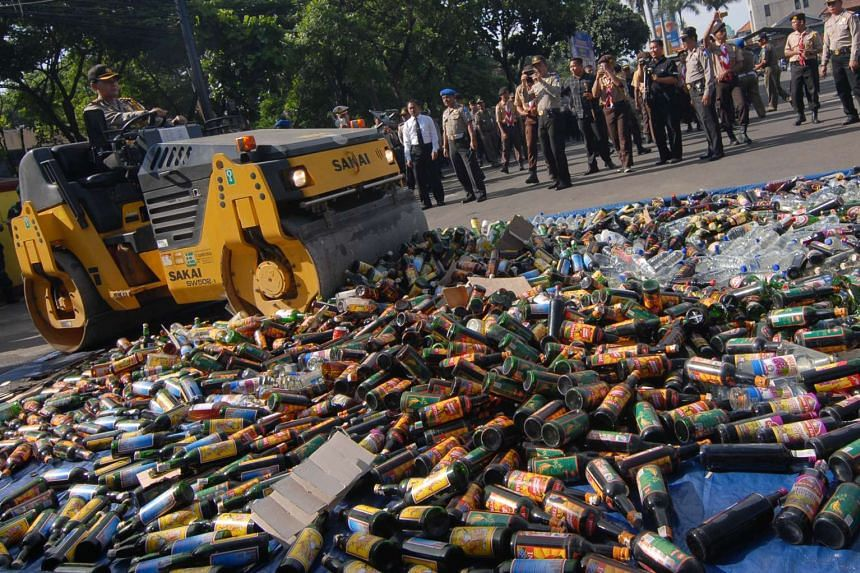 Indonesian police destroy bottles of alcoholic drinks at a police station on Dec 23, 2015.