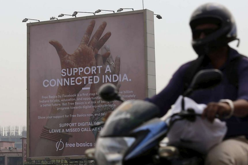 A motorist rides past a billboard displaying Facebook's Free Basics initiative in Mumbai.