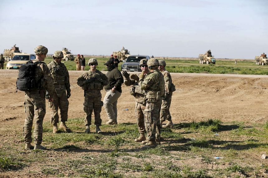 US-led coalition instructors monitor Iraqi soldiers while participating in a joint live ammunition exercise at Besmaya military base in Iraq.