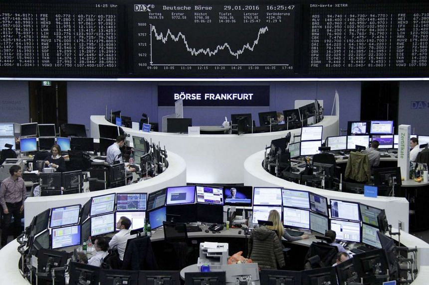Traders work at their desks in front of the German share price index, DAX board, at the stock exchange in Frankfurt, Germany.