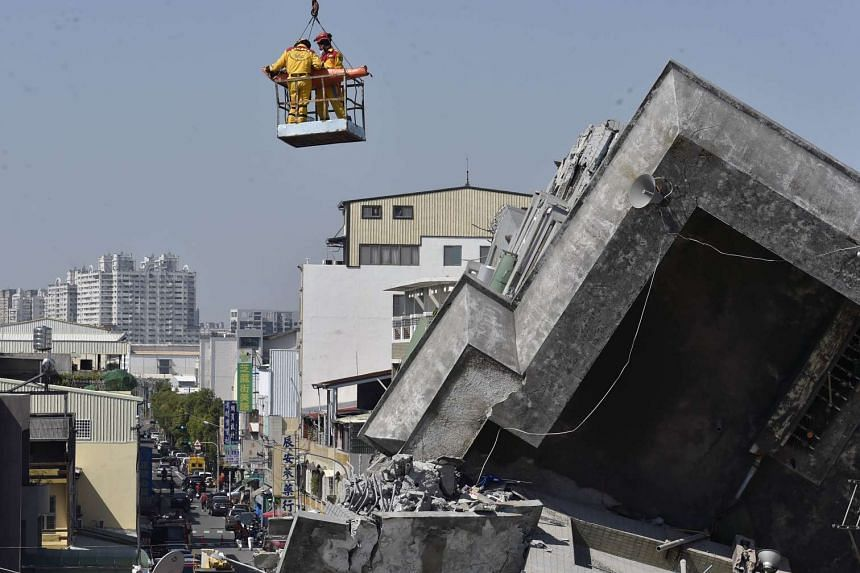 A man is lifted by crane out of the rubble by rescue workers at the Wei-Kuan complex which collapsed int he 6.4 magnitude earthquake in Tainan, Taiwan on Feb 8, 2016.