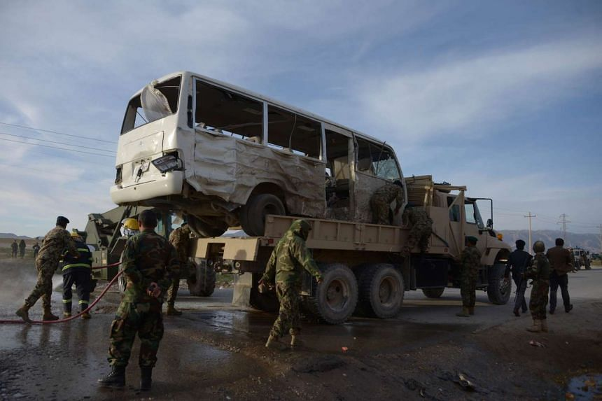 Afghan National Army soldiers stand near a bus damaged by a suicide attack in Dehdadi on Feb 8, 2016.