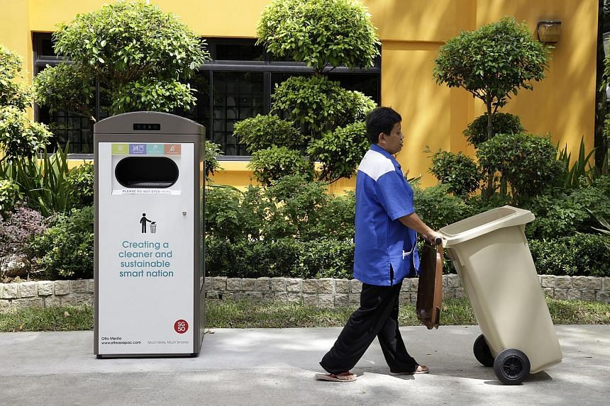 Madam Jamaliyah wheeling a normal bin away from the smart bin, which has a compactor and can store up to eight times more rubbish than a normal bin of the same size.