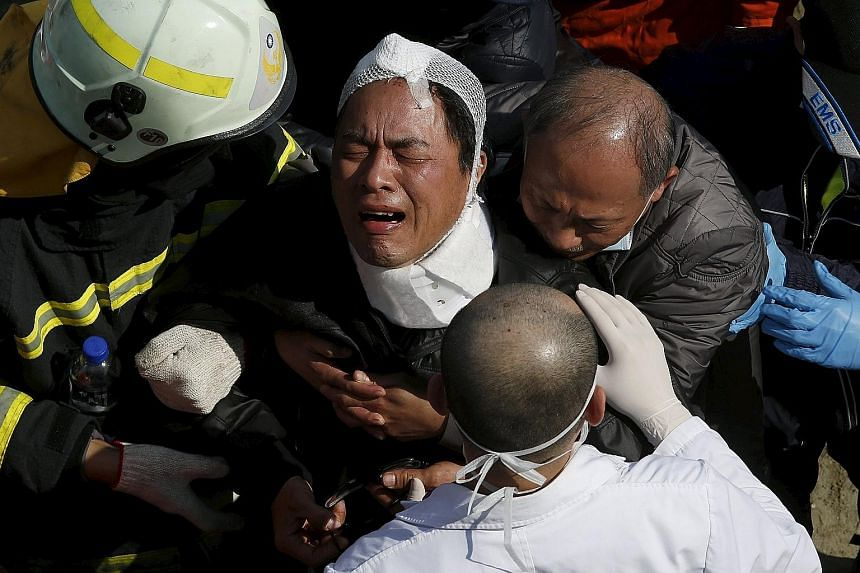 Left: Rescuers searching for survivors following the earthquake in Tainan city. Officials said a probe has been launched as questions have been raised over the safety of the building complex. Below: A man grieving after a family member was confirmed