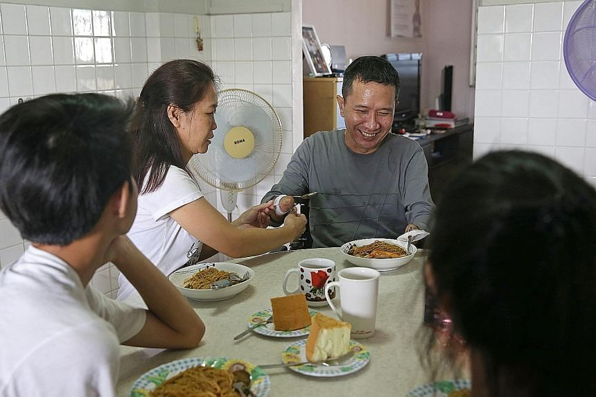 Madam Choong Siet May helping her husband, Mr Tan Whee Boon, to adjust a strap around his arm so that he can hold on to utensils and have lunch with his two teenage children. Mr Tan had four amputations last year after a bout of GBS infection, follow